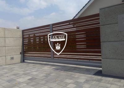 brama aluminiowa przesuwna wkomponowana pomiędzy bloczki z betonu architektonicznego